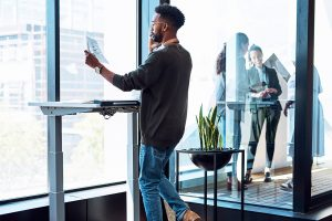 Man stands at work utilizing a convertible desk.