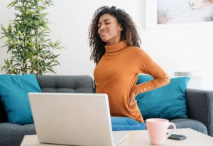 Woman experiences back pain from sitting with improper posture while working from home.